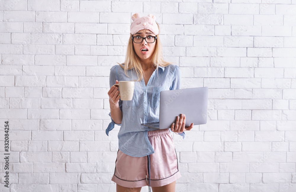 Fototapeta Work from home. Girl in pajamas, sleep mask with cup and laptop