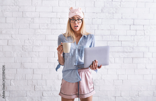 Fototapeta Work from home. Girl in pajamas, sleep mask with cup and laptop obraz