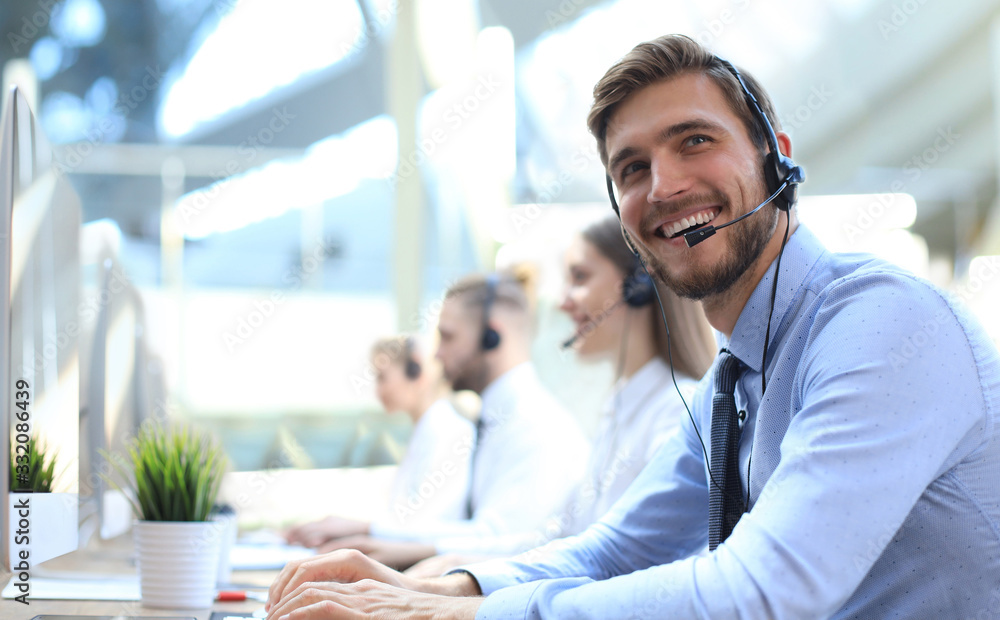 Fototapeta Portrait of call center worker accompanied by his team. Smiling customer support operator at work.
