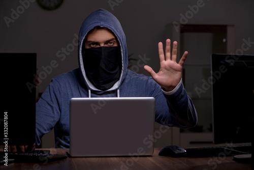Male hacker hacking security firewall late in office Fototapeta