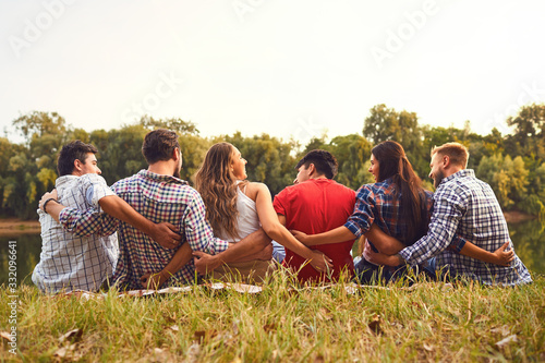 Fotomural Young people sit on the grass hugging in nature in the park