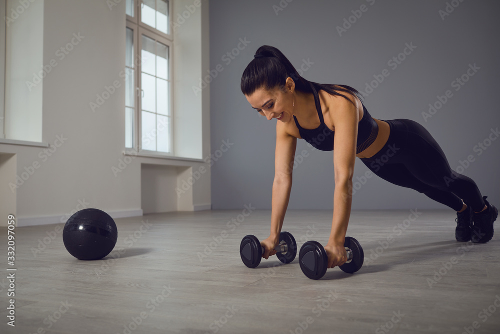 Fototapeta Athletic girl in black sportswear doing push-up exercises in a room indoors.