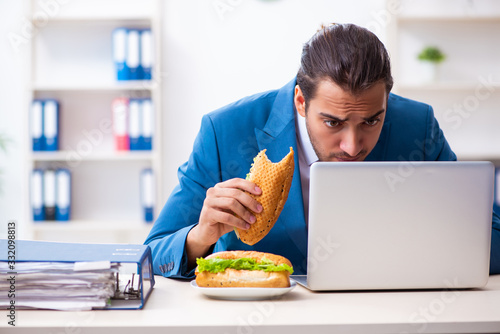 Young male employee having breakfast at workplace Canvas Print