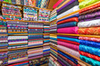 canvas print picture - Colored textile or fabric at a street Asian Market, shelves with rolls of fabric and textiles