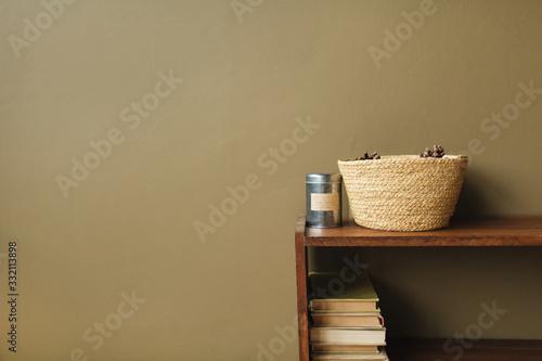 Obraz Modern minimal interior design concept. Straw basket, books on wooden stack on olive background. - fototapety do salonu
