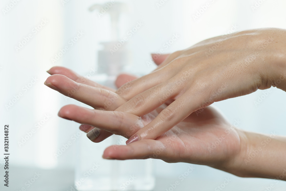 Fototapeta Female hands using wash hand sanitizer gel pump dispenser. Clear sanitizer in pump bottle, for killing germs, bacteria and virus.