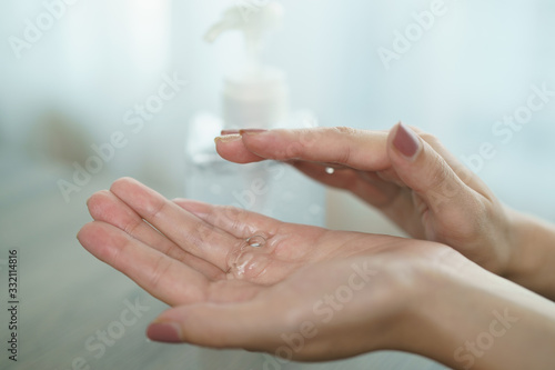 Obraz Female hands using wash hand sanitizer gel pump dispenser. Clear sanitizer in pump bottle, for killing germs, bacteria and virus. - fototapety do salonu