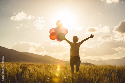 Cheering young asian woman on grassland with colored balloons Fototapet
