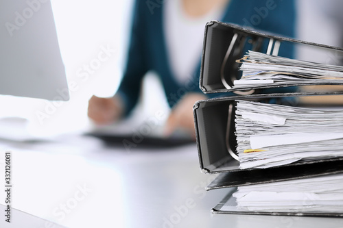 Photo Binders with papers are waiting to be processed by business woman or bookkeeper working at the desk in office back in blur