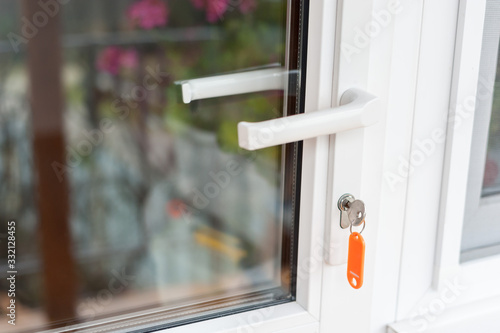 Key in a new white plastic glazed door. Canvas Print