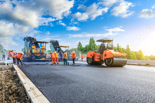 Fotomural Construction site is laying new asphalt road pavement,road construction workers and road construction machinery scene