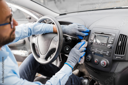 Fototapeta Close up of man hand wearing protective gloves and cleaning car interior dashboard with microfiber cloth. Car detailing or valeting concept. obraz