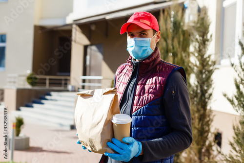 Vászonkép Courier in protective mask and medical gloves delivers takeaway food