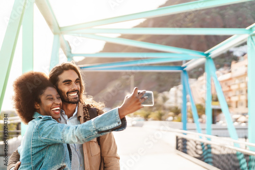 Happy smiling couple taking selfie with mobile smartphone outdoor - Young trendy Fotobehang