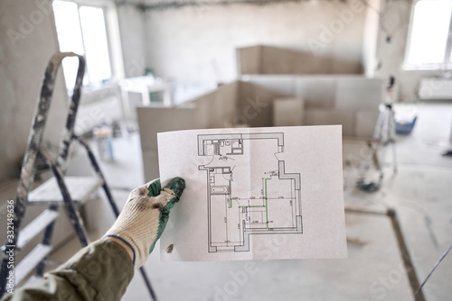 Fototapeta The construction worker hold in hands Architectural blueprints. Repair or construction of a new apartment. Concept for new house design or home improvement. Development of the apartment project. obraz
