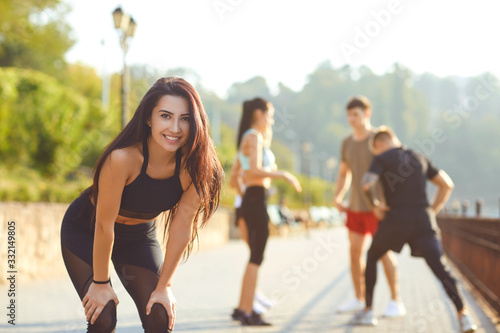 Cuadros en Lienzo Sporty girl smiles on the background of friends athletes in the park