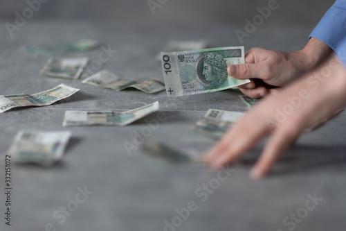 Fototapeta Polka gotówka na stole, ręka trzymająca banknot obraz