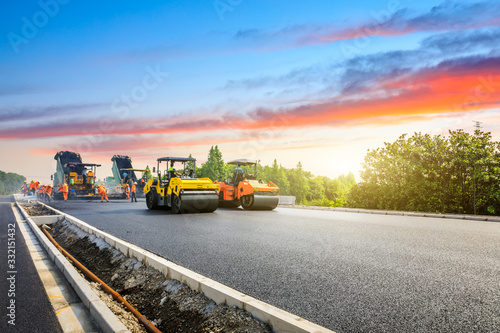 Leinwand Poster Construction site is laying new asphalt road pavement,road construction workers and road construction machinery scene