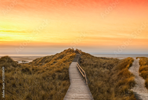 Fototapeta Wooden path and stairs crossing the dunes to the beach of Norddorf, Amrum, in sunset obraz