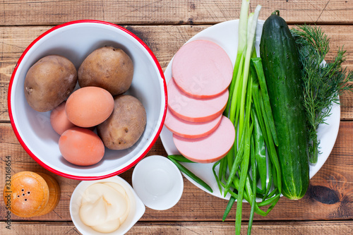 Fototapeta Step by step preparation of cold okroshka soup with sausage, step 1 - preparation of the necessary ingredients, top view, selective focus obraz