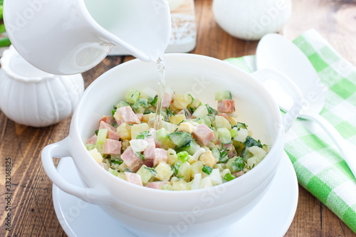 Fototapeta Traditional summer okroshka soup with sausage and vegetables in white miskes with added water, selective focus obraz