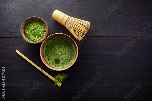 Fototapeta Matcha powder. Organic green matcha tea ceremony. Healthy drink. Traditional japanese drink on black wooden background obraz