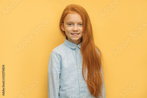 Photo portrait of cheerful positive red haired girl isolated over yellow background