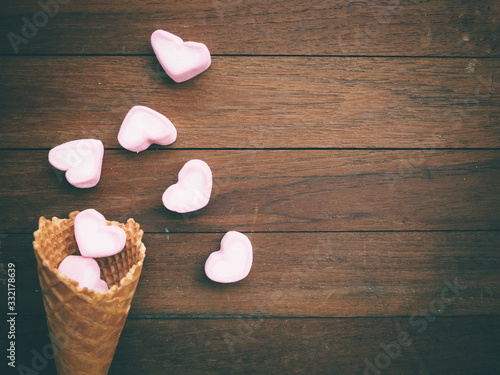Fotografia heart marshmallow are blow away from waffle cone on table