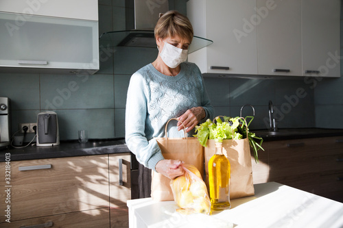 Obraz Seniors woman  wearing medical face mask with food bags at home in the kitchen. quarantine. health concept. Corona Virus. order of products online. Delivering products to home - fototapety do salonu