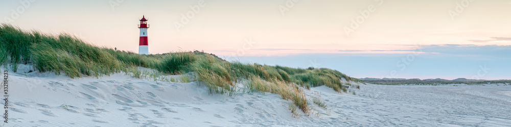 Fototapeta Panoramic view of a lighthouse standing at the coast of Sylt, North Sea, Germany