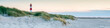 Leinwandbild Motiv Panoramic view of a lighthouse standing at the coast of Sylt, North Sea, Germany