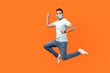 canvas print picture - Full length of positive inspired brunette man with medical mask in sneakers, denim outfit jumping in air or running quickly fast. indoor studio shot isolated on orange background, empty copy space