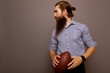 Serious businessman in formal wear with rugby ball isolated on grey background with copy space. Portrait of bearded stylish man holds a game ball in his hands.