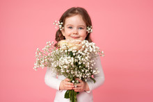 Excited Pretty Little Girl Holding Big Bouquet Of Little Spring White Flowers And Looking At The Camera