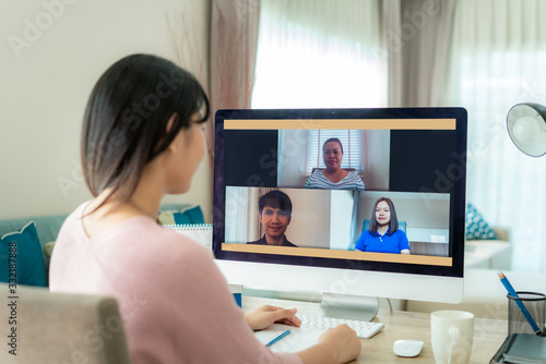 Asian business woman talking to her colleagues about plan in video conference. Multiethnic business team using computer for a online meeting in video call. Group of people smart working from home..
