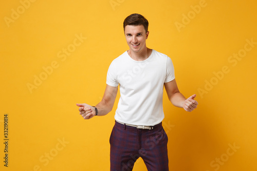 Photo Smiling young man guy 20s in white t-shirt posing isolated on yellow orange background in studio