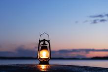 Old Rusty Lantern On The Wet Rock. Beautiful Sunset Sky And Sea On Background. Kerosene Lamp Soft Glow At The Seaside.