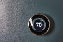 70 Degree Thermostat Isolated On Blue Wall. Nest Thermostat Saving Energy Green Tech. Heating And Cooling Device.
