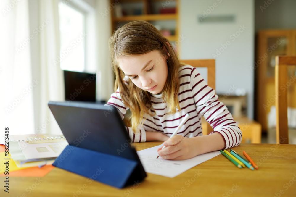 Fototapeta Smart preteen schoolgirl doing her homework with digital tablet at home. Education and distance learning for kids. Homeschooling during quarantine.