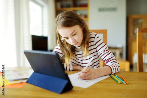 Smart preteen schoolgirl doing her homework with digital tablet at home. Education and distance learning for kids. Homeschooling during quarantine.