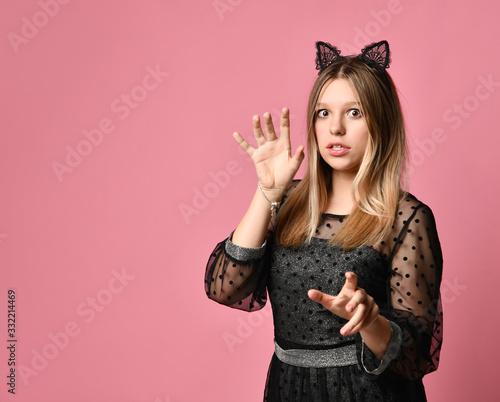 Teen girl in black dress, headband in form of cat ears, bracelet. Acting like...