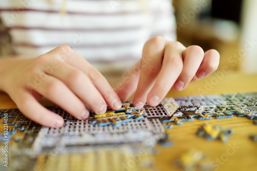 Obraz Close-up on child's hands playing puzzles at home. Child connecting jigsaw puzzle pieces in a living room table. Kid assembling a jigsaw puzzle. Stay at home activity for kids. - fototapety do salonu