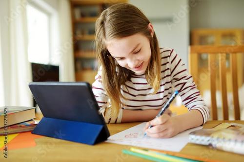 Fototapeta Smart preteen schoolgirl doing her homework with digital tablet at home. Education and distance learning for kids. Homeschooling during quarantine. obraz
