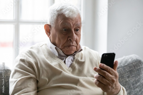 Old man sit on sofa hold smartphone look at device screen feels confused shocked by received sms message Canvas Print