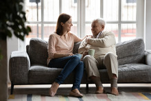 In Cozy Living Room Caring Adult Daughter Drink Tea With Old Dad Family Enjoy Talk Sit On Comfy Couch. Caregiver And Patient Care, Attention, Love, Strong Connection With Older Relative Person Concept