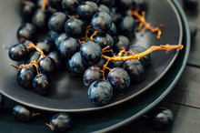 Closeup Of Black Grapes In Black Plates At Wooden Table
