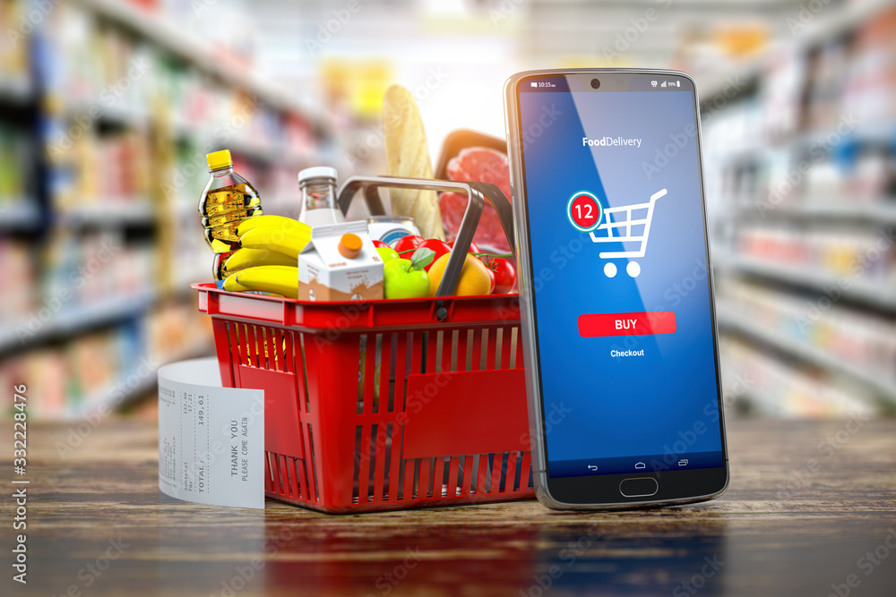 Fototapeta Shopping basket with fresh food and smartphone. Grocery supermarket, food and eats online buying and delivery concept.