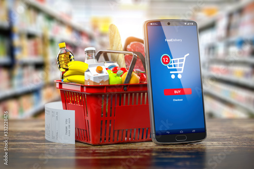 Fotografía Shopping basket with fresh food and smartphone