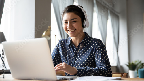 Obraz Smiling Indian girl wearing headphones using laptop, looking at screen, happy young female listening to favorite music while working online on project, excited student learning language - fototapety do salonu