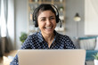 Head shot portrait smiling Indian woman wearing headphones posing for photo at workplace, happy excited female wearing headset looking at camera, sitting at desk with laptop, making video call